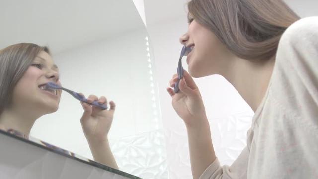 Женщина утром чистит зубы